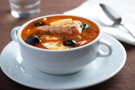 Solyanka, Russian soup with salmon, olives and lemon photo