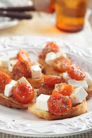 Crostinis with diced feta cheese and cherry tomato photo