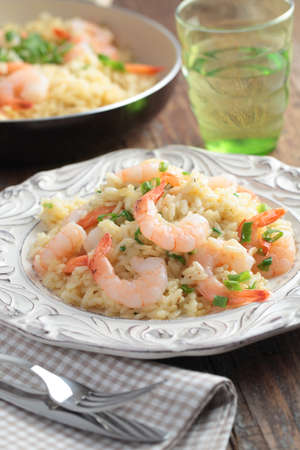 Risotto with shrimps and green onion on a rustic table photo