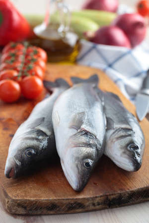 Raw sea bass on a wooden cutting board Stock Photo - 14334421