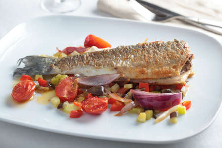 Roasted sea bass with vegetables on a dish photo