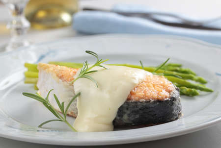 Roasted salmon steak with asparagus and rosemary under cheese sauce photo