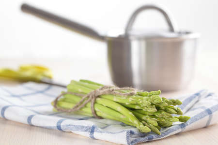 Sheaf of green asparagus against a sauce pan photo
