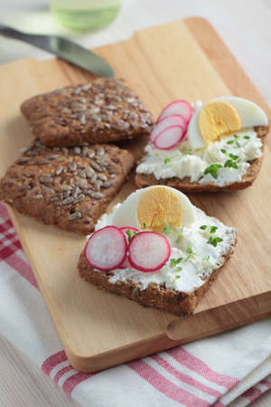 Sandwiches with rye bread, cream cheese, boiled egg, radish, and thyme photo