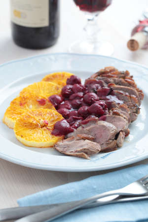 Roasted duck meat with sliced orange and cherry sauce photo