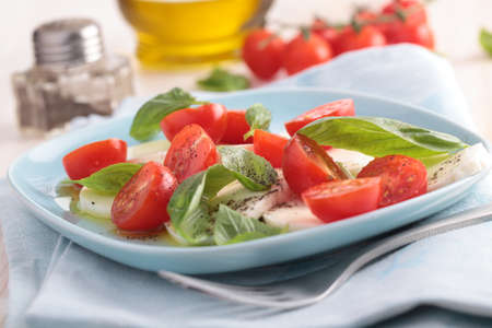 Caprese salad with mozzarella, cherry tomato, and basil on blue plate photo