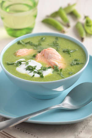 Cream of green pea soup with salmon and sour cream photo