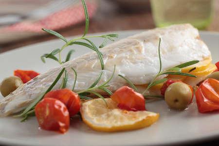 plato de pescado: Lubina al horno con tomate cherry, aceitunas y romero Foto de archivo