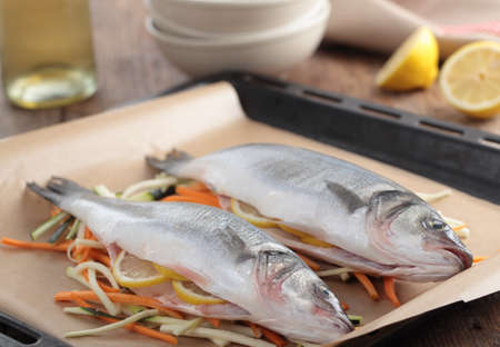 bass fish: Raw sea bass on a bed of vegetables before baking