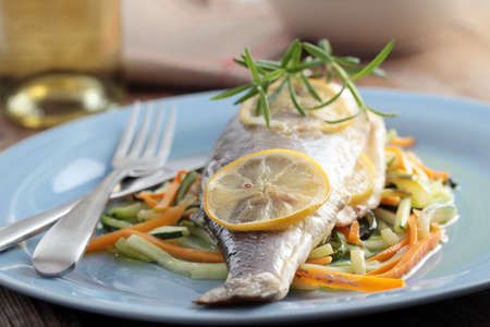 Baked sea bass on a bed of roasted vegetables photo
