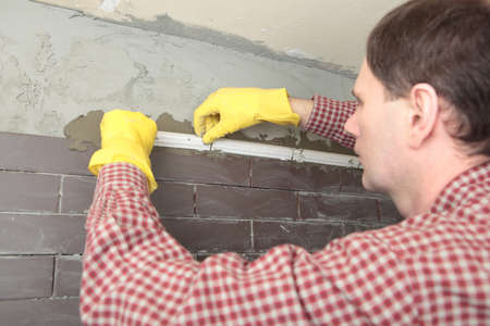putty knives: Contractor installing tiles on a wall Stock Photo