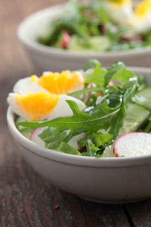 Fresh salad with radish, cucumber, rocket, and boiled egg photo