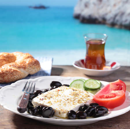 Breakfast with feta cheese, olives, simit, vegetables and tea against Mediterranean sea photo