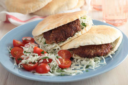 Pita bread filled with breaded steak and cabbage with cherry tomato photo