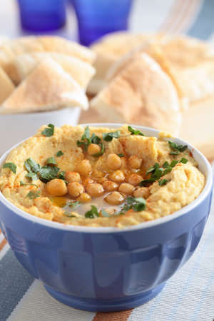 Hummus topped with whole chickpeas, parsley, and olive oil photo