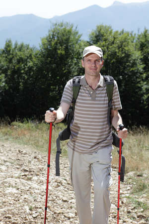 Hiker with trekking poles and backpack on a mountain footpath photo