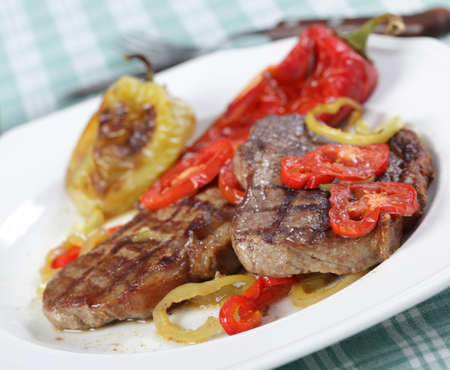 Beef steaks with baked pepper and tomato photo