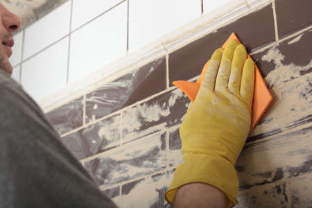Contractor grouting ceramic tiles on a wall photo