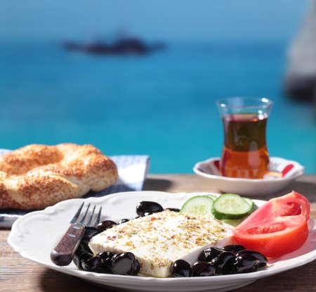 Ontbijt met feta kaas, olijven, simit, groenten en thee tegen Middellandse Zee Stockfoto