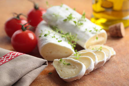 Goat cheese, cherry tomato, and thyme on a wooden cutting board photo
