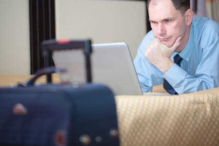 and the horizontal man: Businessman reading news from laptop in a hotel room Stock Photo