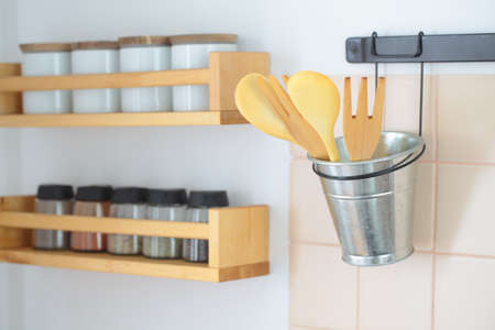 Wooden spatulas in a holder and racks with spices on a kitchen wall photo