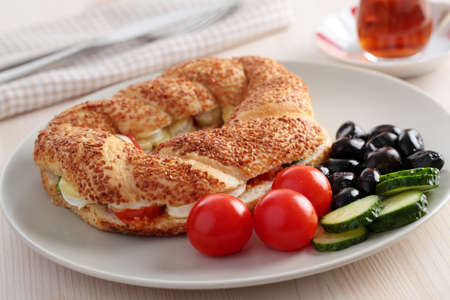 Turkish breakfast with simit, cheese, cherry tomato, cucumber, black olives, and tea