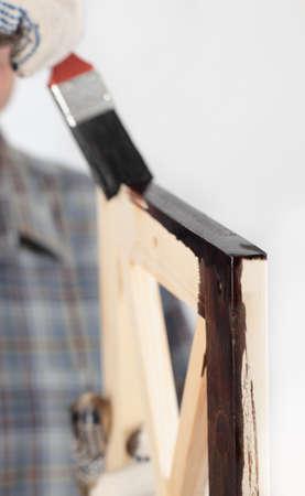 furniture part: Man varnishing a wooden part of furniture using paintbrush