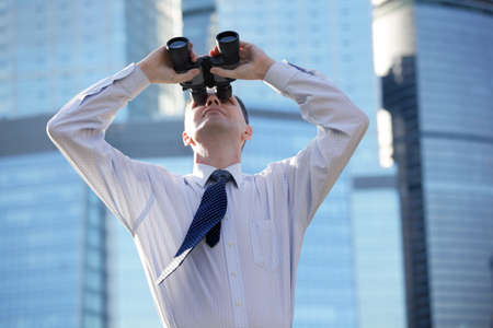 Businessman with binoculars against modern office buildings photo