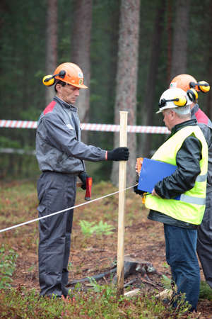 tree felling: Raubichi, Minsk region, Belarus - August 25, 2012: Judges set up the marker post for tree felling during World Logging Championship in Raubichi, Minsk region, Belarus at August 25, 2012 Editorial