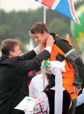 tree felling: Raubichi, Minsk region, Belarus - August 25, 2012: First Deputy Minister of forestry of republic of Belarus Fiodor Lisitsa hands over silver medal in tree felling to Matthew Thomas, UK, during World Logging Championship in Raubichi, Minsk region, Belarus  Editorial