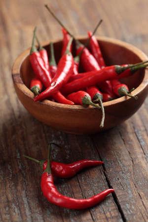 Rode chili pepers in een houten kom Stockfoto