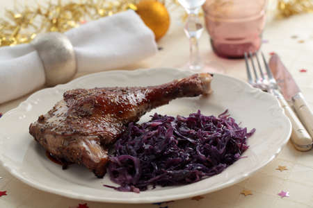 Roasted goose leg with braised red cabbage on a Christmas table photo