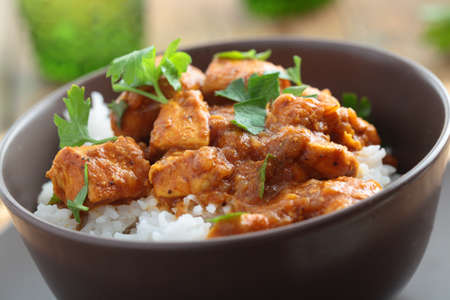 british food: Chicken curry with rice and parsley in a bowl