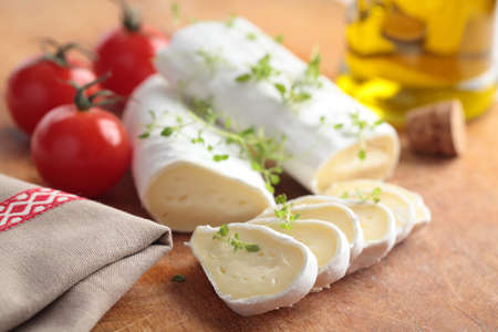 Goat cheese, cherry tomato, and thyme on a wooden cutting board