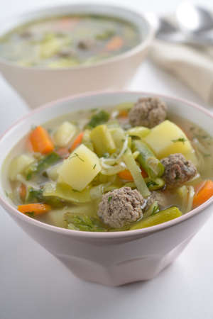 Meatball soup in two bowls photo