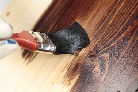 Vernissen van een houten plank met penseel Stockfoto