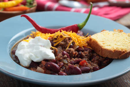Chili con carne with Cheddar cheese and sour cream photo