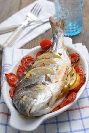 Baked gilt-head sea bream with tomato, sliced lemon, and lemongrass Stock Photo - 15729889
