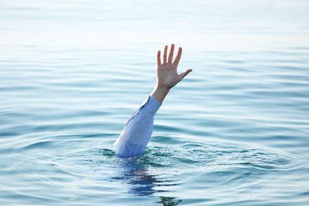 Hand van de zakenman verdrinken in de zee