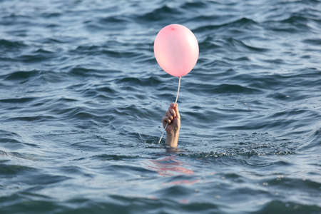 in need of space: Hand of drowning man catching a balloon Stock Photo