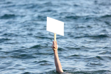 Hand with blank banner among a sea photo