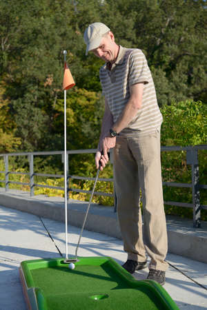 Man with putter make a stroke on a minigolf course photo