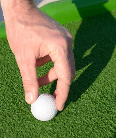 Man setting up a minigolf ball on a golf course photo