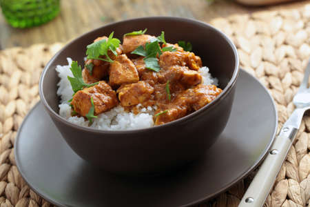 Chicken curry with rice and parsley in a bowl