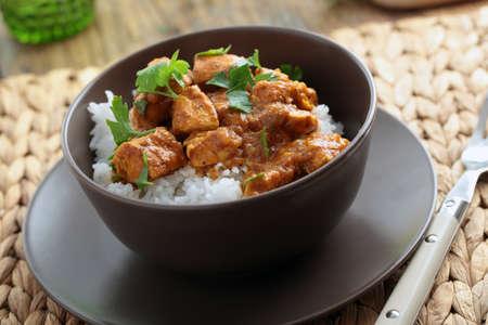 Kip curry met rijst en peterselie in een kom
