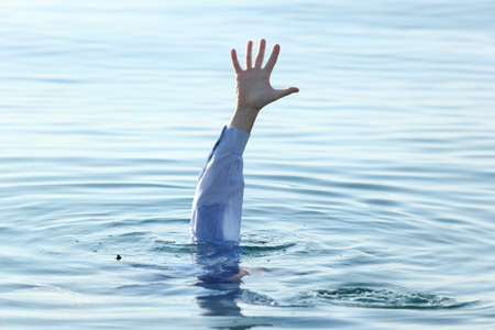 Hand of businessman drowning in the sea photo