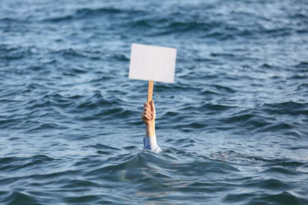 sinking: Hand with blank banner among a sea