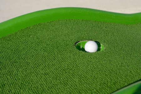 Minigolf ball gets to a hole photo