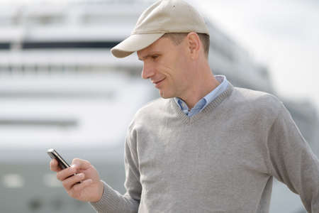 Tourist reading SMS on his mobile phone against a cruise ship photo